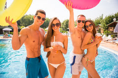 Swimming pool. Beautiful young people having fun in swimming pool with colored rubber rings Royalty Free Stock Photo