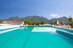 Swimming pool besides mountains Stock Photo