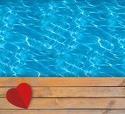 Swimming pool with blue clear water, wooden deck and red paper Royalty Free Stock Images