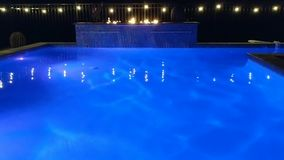 Swimming Pool With Blue Colored Lights, Waterfall, Flames And Lights. Swimming pool at night with blue color changing lights, hanging white lights on a fence, a stock video footage