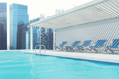 Swimming pool with blue deck chairs, city Stock Image