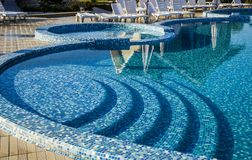 Swimming pool with blue mosaic. Curved steps to the swimming pool with blue mosaic tiles Royalty Free Stock Photography