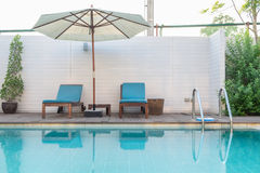 Swimming pool blue sunbed umbrella Royalty Free Stock Images