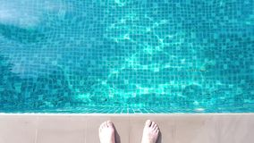 Swimming pool blue water and foot on edge in summer and white side bar floor tiles in hotel for represent relaxation stock video footage