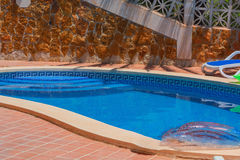 Swimming pool with blue water to relax. Luxury swimming pool with beautiful landscaping of the territory. In the background a mediterranean wall decorated with Stock Photography