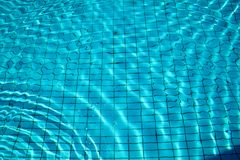 Swimming pool bottom caustics ripple and flow with waves. Stock Photos