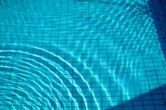Swimming pool bottom caustics ripple and flow with waves. Stock Photo