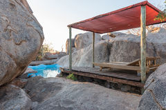 Swimming pool between boulders on a hill at Hoada Camp. HOADA, NAMIBIA - JUNE 27, 2017: A swimming pool hidden between boulder on a hill at the Hoada Camp, in Royalty Free Stock Image