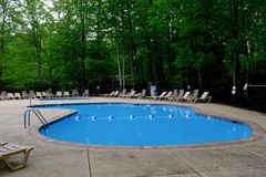 Pool Deck and Lounge Chairs in Green Forest. Swimming pool with bright blue water, surrounded by lounge chairs and thick dark forest of green trees royalty free stock photography