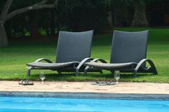 Swimming pool with 2 chairs Stock Photos