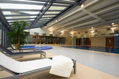 Swimming pool and chaise-longue with towel. In Hotel Leisure Center Interior stock images