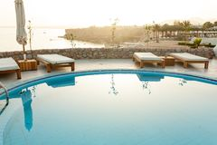 Swimming pool with chaise lounge and sunshade at tropical resort. Summer evening stock photos