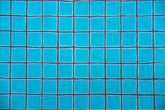 Swimming pool clear water showing turquoise blue clay square tiles and grey cement grout lines underwater wave copyspace Royalty Free Stock Image