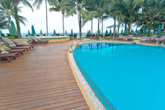 Swimming pool with coconut and ocean background Royalty Free Stock Photo