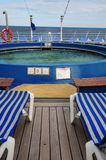 Swimming pool on cruise ship. Close up of small swimming pool on deck of cruise ship, sun loungers in foreground Stock Image
