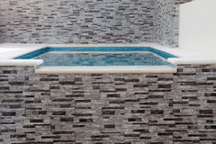 Swimming pool with crystal clear water and gray stone walls. Above ground swimming pool with crystal clear water and gray stone walls Stock Photo