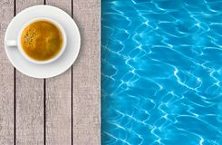Swimming pool and cup of coffee on deck Stock Photography