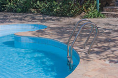 Swimming pool in curved shape with stair. Stock Photo