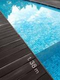Swimming pool & dark wood deck, depth marking Royalty Free Stock Images