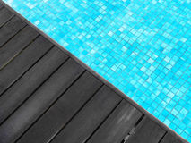 Swimming pool & dark wood deck Royalty Free Stock Photos
