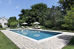 Swimming pool with deck chairs. Swimming pool of luxury home with deck chairs Stock Images