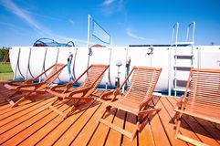 Swimming pool deck chairs. Several wooden deck chairs next to a garden swimming pool Stock Photo