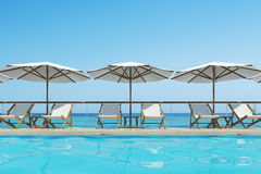 Swimming pool with deck chairs, umbrellas, front. White deck chairs are standing under beach umbrellas near a swimming pool. A blue cloudless sky is above them Stock Photos