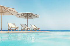 Swimming pool, deck chairs, umbrellas, horizon. Three white deck chairs are standing under beach umbrellas near a swimming pool. A blue cloudless sky is above Stock Photo
