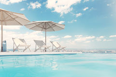 Swimming pool with deck chairs, umbrellas, sky Royalty Free Stock Image