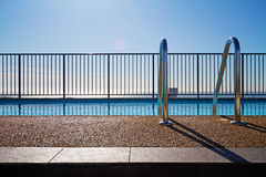 Swimming pool edge with ladder and sky background Stock Photos