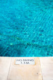 Swimming pool edge with `No Diving` warn sign Stock Photo
