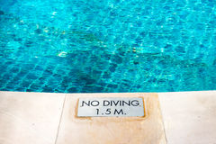 Swimming pool edge with `No Diving` warn sign Stock Images