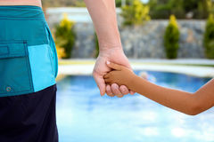 Swimming pool. Father holds the hand of a small child on a blue  background Royalty Free Stock Image