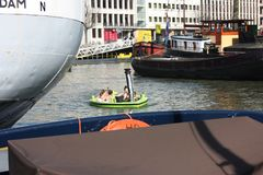 Swimming pool floating in the water of the river or canal of the port of Rotterdam. Young Dutch students have fun and spend time royalty free stock photo