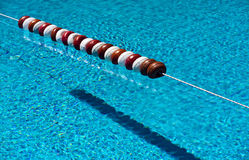 Swimming Pool Floats. Alternating red and white floats on a rope dividing the swimming pool Royalty Free Stock Photo