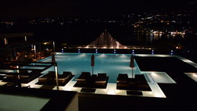 Swimming pool with fountain in night illumination at the luxury hotel. Crete, Greece stock video