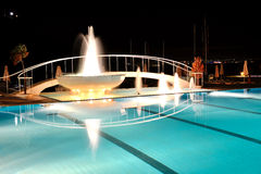 Swimming pool with fountain in night illumination Royalty Free Stock Photography