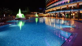 The swimming pool with fountains in night illumination