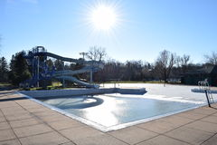Swimming Pool Frozen Ice On Sunny Winter Day Waterslide In Background Stock Photo