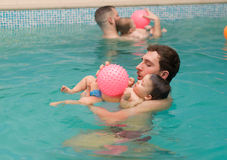 Swimming pool fun. POZNAN, POLAND - JANUARY 03, 2015: Man playing with a baby in the swimming pool at a local club Royalty Free Stock Photos