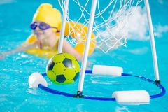 Swimming Pool Games. Children Playing with Ball in the Pool royalty free stock images