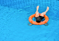 Swimming pool games. Little kid plays with orange ring buoy in swimming pool royalty free stock photos