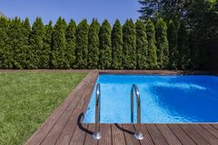 Swimming pool in the garden with trees and green grass during summer. Real photo. Concept stock images