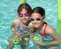 Swimming pool girls. Two young girls wearing goggles in swimming pool floating on noodles Stock Photos