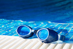 Swimming pool goggles on the poolside. Image of a swimming pool goggles on the poolside royalty free stock images