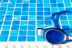 Swimming pool goggles on the poolside Stock Photography