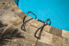 Swimming pool. Grab bars ladder in the blue swimming pool Royalty Free Stock Photo