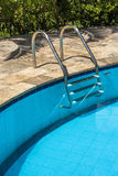 Swimming pool. Grab bars ladder in the blue swimming pool Royalty Free Stock Photos