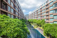 Modern condominium building. Swimming pool with green trees among high rise modern condominium building, condominium with pool in DCondo Creek on Phuket royalty free stock photo