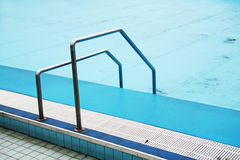 Swimming pool and hand rail. Blue water in swimming pool with hand rail in foreground Stock Photo
